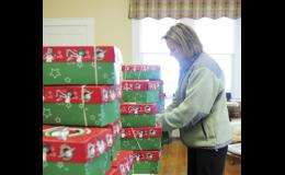 Kim Johnson, Operation Christmas Child volunteer coordinator, binds donated boxes with rubber bands at the Joshua's Way collection site Tuesday.
