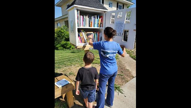 A mother with her son stopped by the Little Library last week to choose some books.