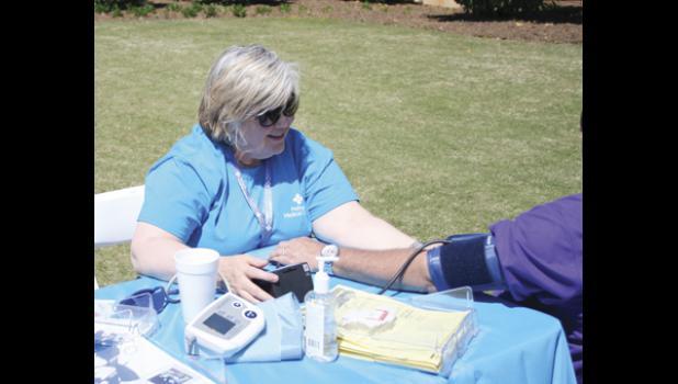 A representative from Pelham Medical Center performs a free blood pressure check on a festival goer during the 2014 Pelham Medical Center Greer Family Fest.