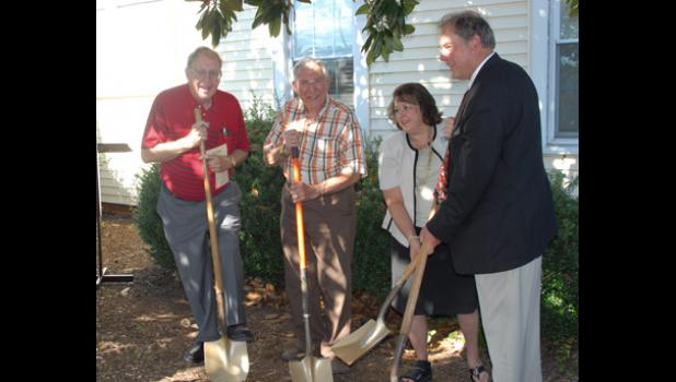 Board members James Hayes, Russell Ashmore and Mike Burns break ground for the Taylors Free Medical Clinic expansion with Karen Salerno, the clinic's executive director. 