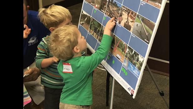 Twin brothers Mack and Charlie Ringer offer their suggestions at the public input meeting for a new Kids Planet design Tuesday night.