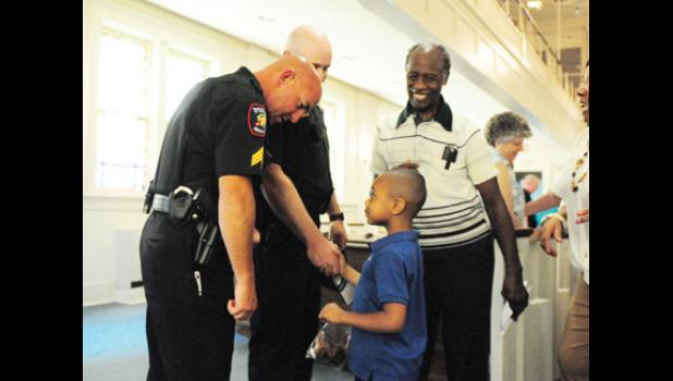 Sgt. Jeff Smith, left, and Sgt. Randle Ballenger greeted members of the community at a prayer service at Greer First Baptist Church Monday afternoon.