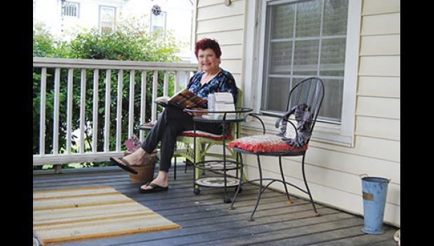 Susan Christmas of Greer sits on her porch many mornings and evenings, interacting with neighbors who come to claim books from her Little Library.