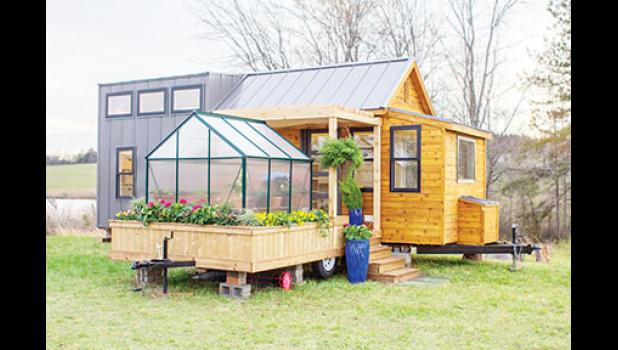 The Hanson and Aho families work on building a tiny home while being filmed for the  television show, 'Tiny House, Big Living.'