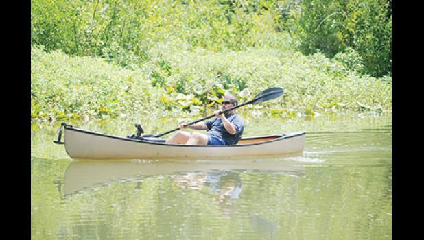 Devin Bonham paddles a boat around Lake Cunningham, located north of Greer.
