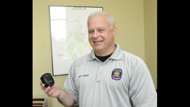 Capt. Matt Hamby holds one of the 12 body cameras Greer police purchased for officers.  The department hopes to soon have every officer wearing one.