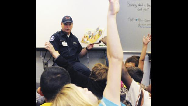 Scott Tompkins of the Greer Fire Department reads to a fifth grade class at Chandler Creek Elementary Tuesday morning, as part of the Real Men Read program.