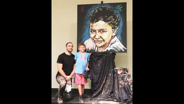 Jared Emerson painted Skyla Frocier's portrait in front of Mountain View Elementary School last Friday.