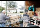 Kenny Gilbert, left, and Keith Dammann load boxes filled with donations for Samaritan's Purse on a conveyor for David Nabors to stack in the transfer truck at Joshua's Way on Poinsett Street.