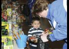 Riverside's Caleb Carithers helps 4-year-old Jonathan Avila fill his toy bag during Saturday's Cops for Tots Toy Drive hosted by The City of Greer Police Department.