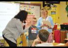 Second-grader Benson Taylor high fives Magic 98.9's Sheri Taylor with Woodland Elementary teacher Theresa Franklin standing by her student. Benson and his mother Shannon Taylor nominated Franklin for the radio station's 'Teachers Who Make Magic' award.