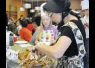 Plate 108 owner Wendy Watkins carves a turkey  as Rheanna Atherton waits to be served.